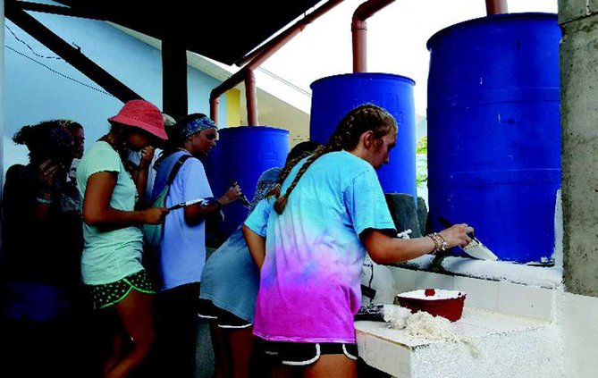 Trip participants paint bathrooms and the new rainwater collection system that provides fresh and running water.